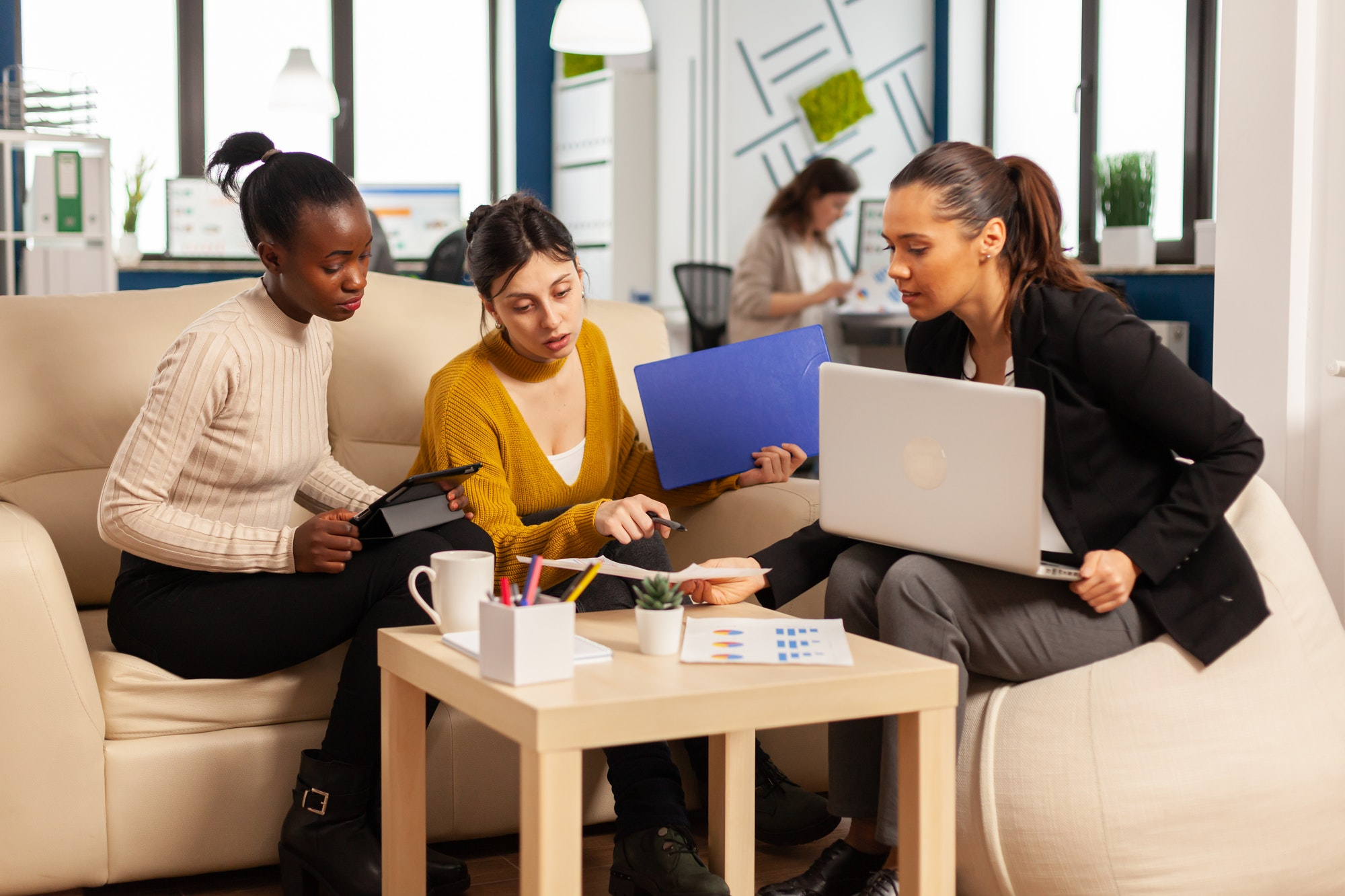 Diverse group of business women sitting on couch in startup company
